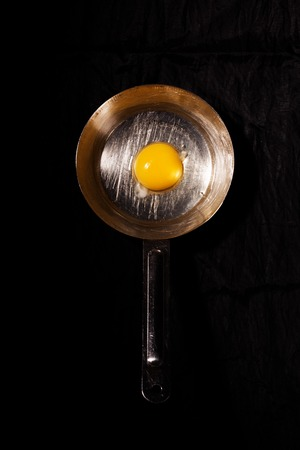 Raw egg in a metal griddle on a black background