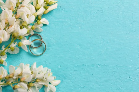 White acacia flowers and two wedding rings on a blue background Stock fotó
