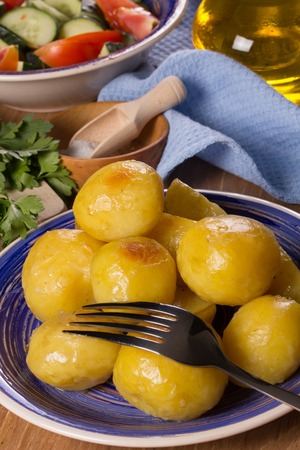 Deep-fried potatoes, salad, vegetable oil on the kitchen table
