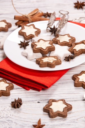 Festive concept with napkin, cookies and spices on a worn white wooden background Stock Photo