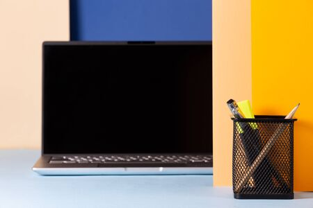 Office concept with laptop and stationery on a background in blue and yellow tones