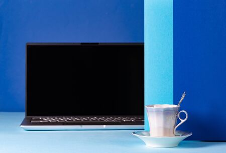 Office concept with laptop and a cup of coffee on a background in blue tones