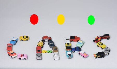 trafic stop: Toy cars spelling out the word cars, with red, yellow, and green trafic lights.