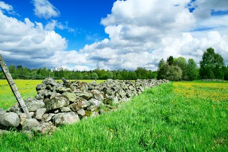 separating: A stone fence separating farm grounds Stock Photo