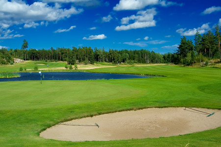 water hole: A bunker, a green, and a pond on a golf course