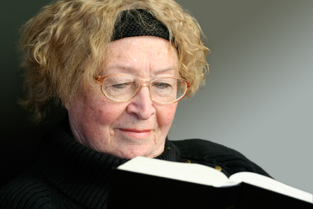 grizzled: Senior woman reading Bible isolated on soft artificial background. The Bible is lit by rays of the Holy Light.