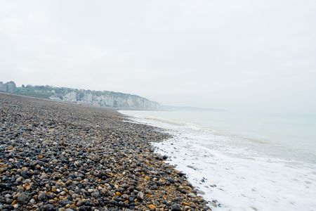 melancholic: Pebble beach and shoreline at the Alabaster Coast in Dieppe, France. Quiet melancholic day in October.