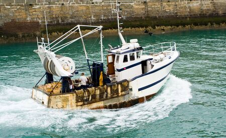 returning: A fishin boat returning to the harbor of Fecamp, France Stock Photo