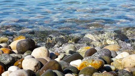 Pebble and pure sea water at sunny summer day, close up view