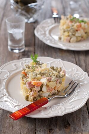 russian salad: Russian salad and a gliss of vodka, selective focus Stock Photo