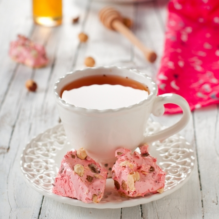 strawberry nougat and cup of tea, square image Stock Photo