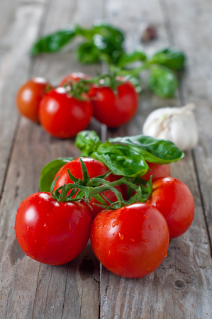 Fresh sweet tomato and basil on the wooden table, selective focus Stock Photo