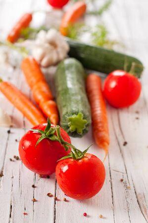 Raw carrot, tomato, garlic and zucchini, selective focus photo