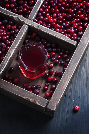 Fresh cranberry juice on the wooden table, selective focus