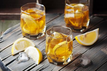 bebidas frias: Whisky fría con hielo y limón en la mesa de la vendimia, foco selectivo