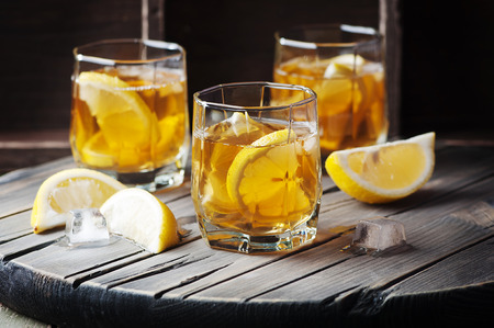 cocktail drinks: Cold whiskey with ice and lemon on the vintage table, selective focus Stock Photo