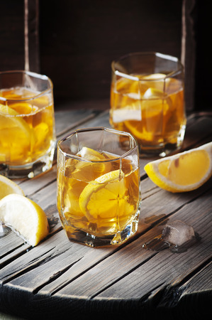 Cold whiskey with ice and lemon on the vintage table, selective focus Stock Photo