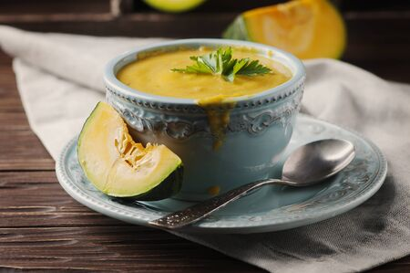 Pumpkin soup with parsley on vintage table, selective focus Stock Photo