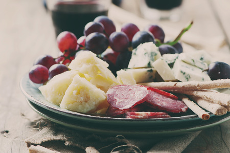 Antipasto with cheese, sausage and grape, selective focus and toned image
