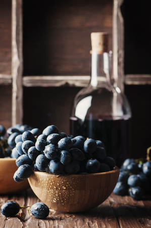 Fresh grape and red wine on the vintage table, selective focus Stock Photo