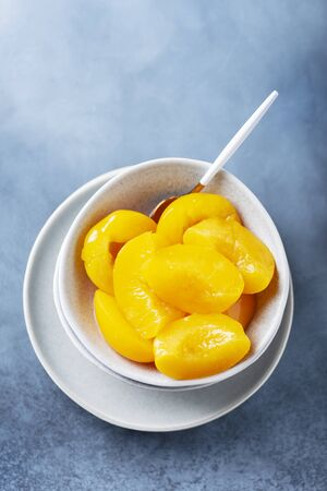Sweet canned peaches in the ceramic bowl, selective focus image