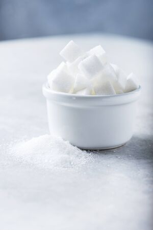 Sugar cubes and grain of sugar on tje light background, selective focus
