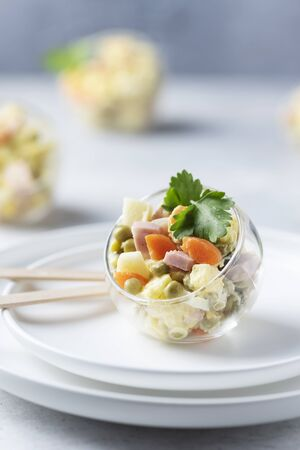Traditional Russian salad Olivier with vegetables, ham and mayonnaise, selective focus image