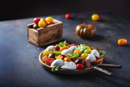 Healthy salad with mozzarella, colored tomatoes and origan, selective focus image