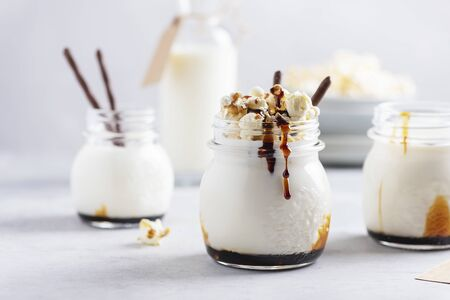 Smoothie with milk, caramel and sweet popcorn, selective focus image