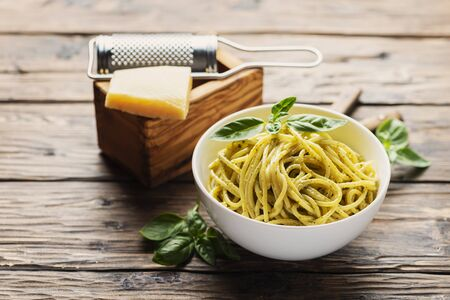 Traditional ligurian spaghetti with basil and cheese, rustic style and selective focus