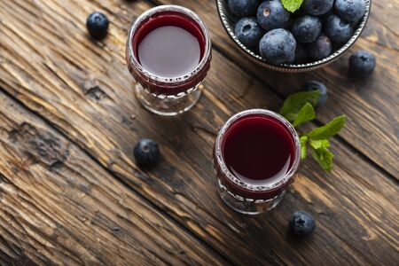 Sweet blueberry liqueur on the wooden table, selective focus image