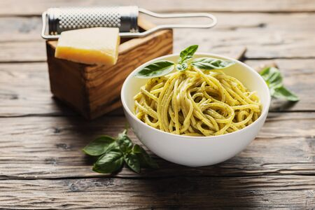 Traditional ligurian spaghetti al pesto with basil and cheese, rustic style and selective focus