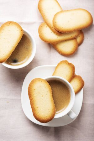 Italian traditional cookies Cat tongues with coffee, selective focus image