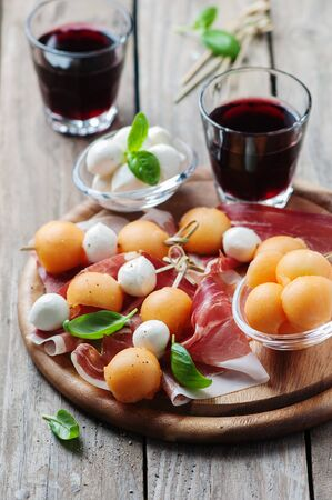 Healthy appetizer with melon, ham and mozzarella, selective focus