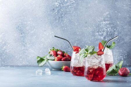 Bar concept. Red cocktail with ice and fresh strawberry on the blue background. Selective focus image with a copy space for your text