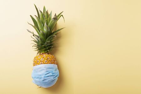 Concept of summer vacation 2020. Pine apple with a medical mask on the yellow background. Top view image