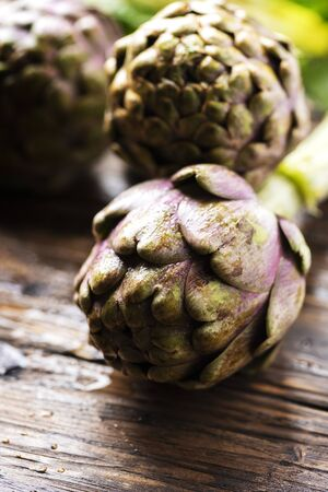 Raw italian artichoke on the wooden table, selective focus image