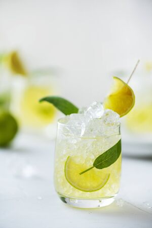 Summer cocktail with sage, lime, peach juice and ice, selective focus Фото со стока