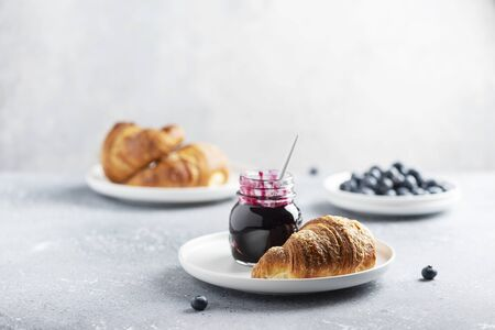 Concept of breakfast with croissant and blueberry jam, selective focus image