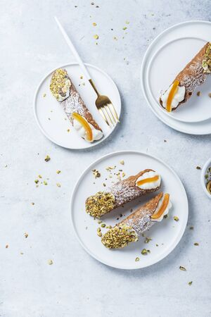 Traditional italian dessert cannoli siciliani on the light background, top view image with a copy space for your text