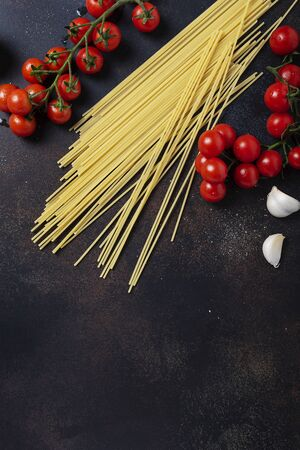 Ingredients for cooking italian pasta: spaghetti, tomato and garlic on the black table. Top view image with a copy space