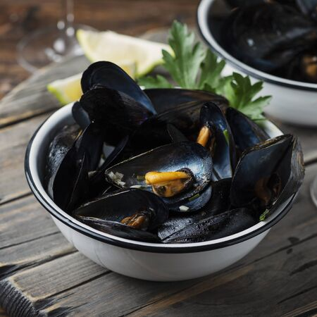 Cooked mussels with parsley and white wine on the wooden table, selective focus image