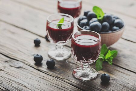 Sweet blueberry liqueur on the wooden table, selective focus and toned image