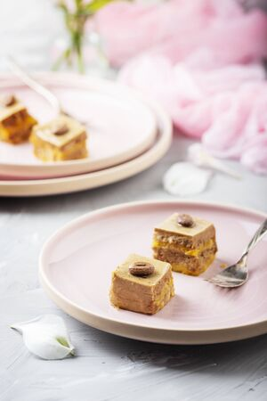 Tasty small cakes with coffe mousse on the pink elegant dish, selective focus