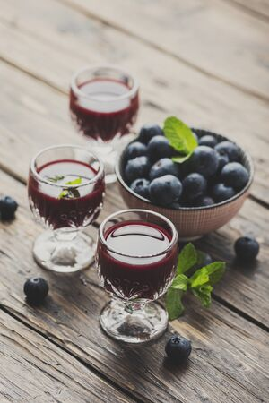 Sweet blueberry liqueur on the wooden table, toned image