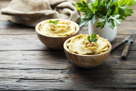 Traditional Middle east appetizer Hummus served with fresh parsley, rustic style and selective focus