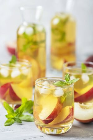 Summer cold tea with peaches and mint, selective focus