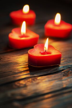 red heart shaped candles on the wooden table, selective focus
