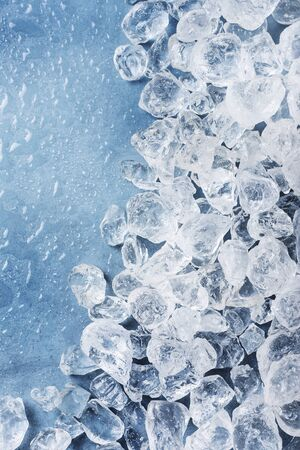 Different crystals of ice on the blue background, selective focus image with a copy space