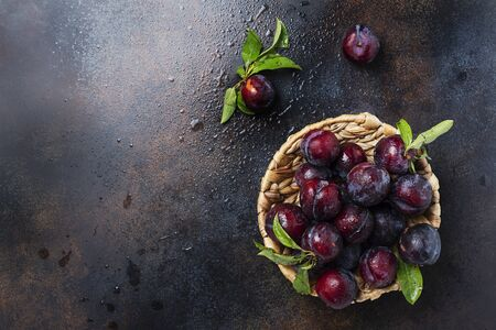 Concept of healthy vegan food. Top down view of sweet plums with green leaves. Image with copy space for your text Stockfoto